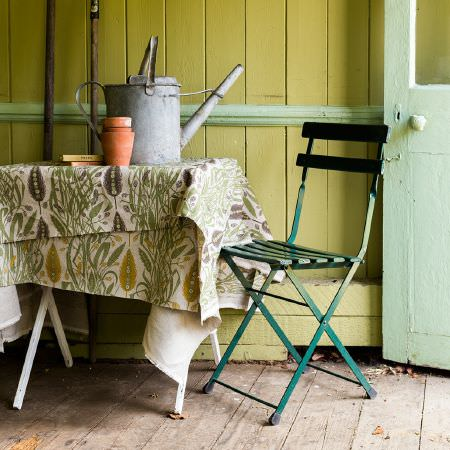 St Judes -  Angie Lewin Fabric Collection - Wooden folding chair painted Robin Hood green, with cream, green and gold/brown leafy fabric, white table, plant pots and metal watering can