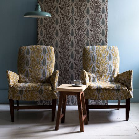 St Judes -  Angie Lewin Fabric Collection - Armchairs with a busy cream, gold and green pattern, matching fabric with brown instead of gold, teal metal ceiling light, and wooden table