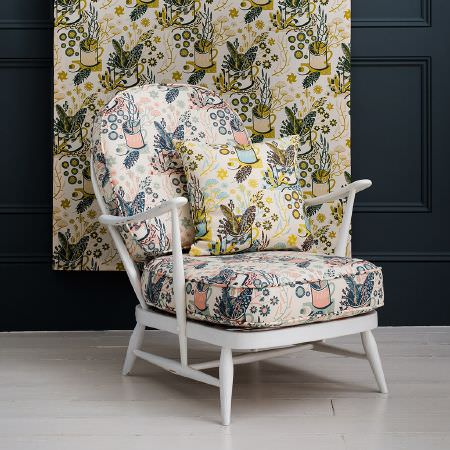 St Judes -  Angie Lewin Fabric Collection - Low white wooden framed chair with busy navy and peach coloured fabric seat cushions, with matching yellow and blue cushion and fabric