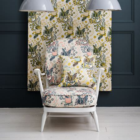 St Judes -  Angie Lewin Fabric Collection - Repeated pattern of flowers in a mug on fabric, a cushion, a white chair