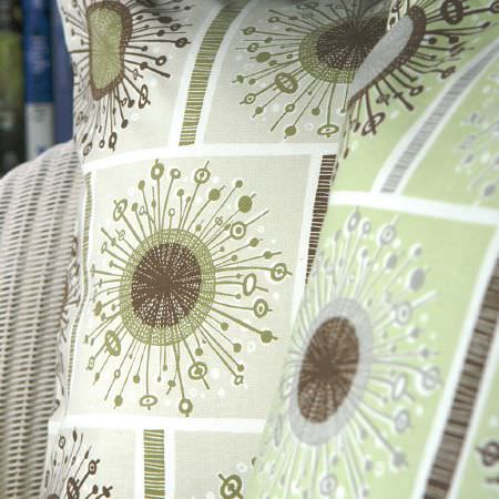 St Judes -  Angie Lewin Fabric Collection - White wicker chair with two green, brown and cream cushions, each with squares containing a geometric starburst shaped design