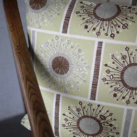 St Judes -  Angie Lewin Fabric Collection - Grey and brown circular and line design on green squares, on a cushion, with a wooden pole