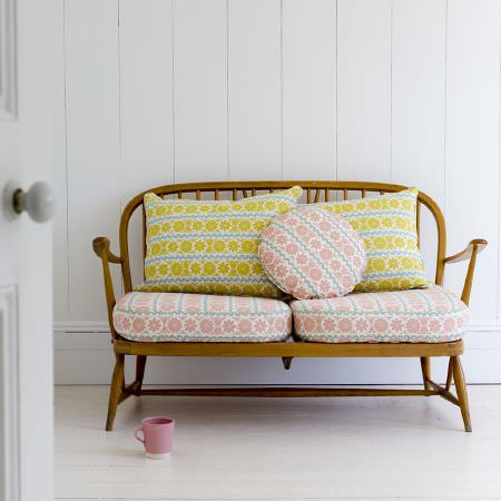 St Judes -  Angie Lewin Fabric Collection - Wooden framed bench with pink, blue and cream patterned seat cushions, matching yellow, blue and cream back cushions, with a pink mug