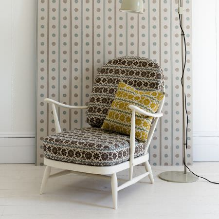 St Judes -  Angie Lewin Fabric Collection - Low wood framed chair painted white, with brown, blue, cream and gold seat and scatter cushions, striped and dotted fabric, cream floor lamp