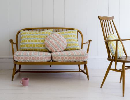 St Judes -  Angie Lewin Fabric Collection - Simple wood chair and bench, with round and square pink or yellow floral patterned cushions, pillow, seat cushions, and a pink mug