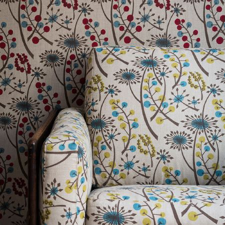 St Judes -  Angie Lewin Fabric Collection - Wood panelled chair with seat, back and arm cushions in cream, blue and green modern floral print, with matching red, blue, cream wallpaper