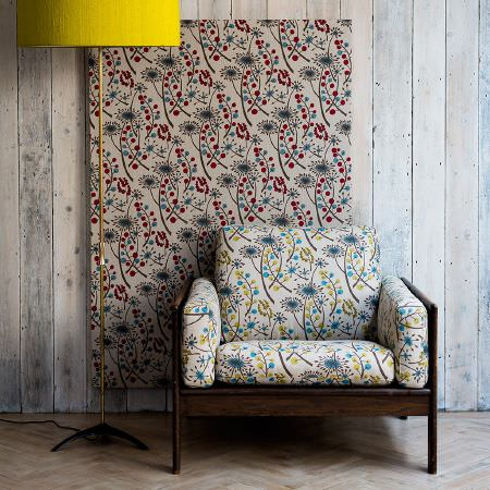St Judes -  Angie Lewin Fabric Collection - Bright yellow shaded floor lamp, with panel of floral patterned fabric, and wooden framed armchair with differently coloured floral cushions