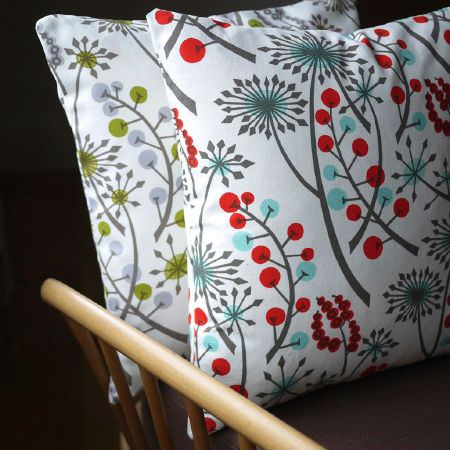 St Judes -  Angie Lewin Fabric Collection - Red, cyan, white and grey cushion, and a green, white and grey cushion, both with the same stylised floral print, both on a wooden chair