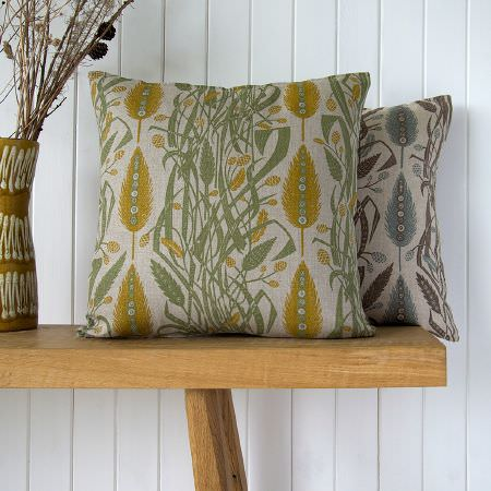 St Judes -  Angie Lewin Fabric Collection - Two wheat sheaf and leaf print cushions; one in cream, gold and green, one in cream and blue, on a wooden bench, with a ceramic vase