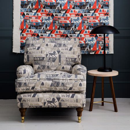 St Judes -  Ed Kluz Fabric Collection - Armchair covered in grey lion, transport, building fabric, with a matching coloured backdrop, a round wood side table and a black domed lamp