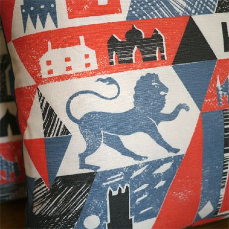 St Judes -  Ed Kluz Fabric Collection - Close-up of a red, blue, black and white cushion, focusing on a lion and building details