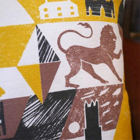 St Judes -  Ed Kluz Fabric Collection - Close-up detail of a cushion with lions, triangles, buildings and night scenes in mustard yellow, white, brown and black