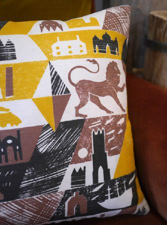St Judes -  Ed Kluz Fabric Collection - Brown, black, white and mustard yellow cushion with a printed pattern of lions, buildings, castles, boats and triangles
