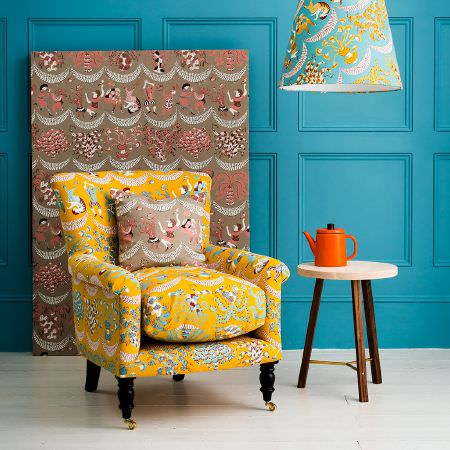 St Judes -  Ellie Curtis Fabric Collection - Bright yellow patterned armchair, brown and salmon coloured fabric, summery patterned lampshade, round wood side table, orange teapot