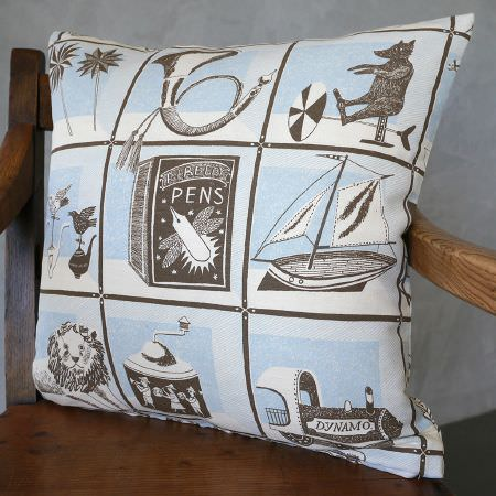 St Judes -  Emily Sutton Fabric Collection - Vintage toy print cushion in brown, white and light blue, featuring trumpets, windmills, boats, and more, on a brown wood chair