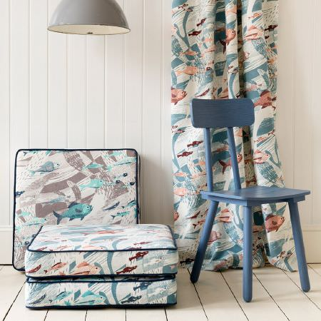 St Judes -  Emily Sutton Fabric Collection - Square fish print seat cushions with blue piping, matching curtains, a blue painted wooden chair, and a grey metal ceiling light lampshade