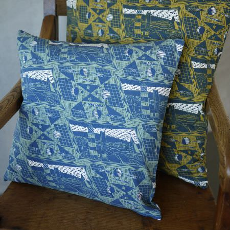 St Judes -  Jonathan Gibbs Fabric Collection - Geometric starry sky and coastal scene print cushions, one in blue and white, one in green and white, on a wooden chair