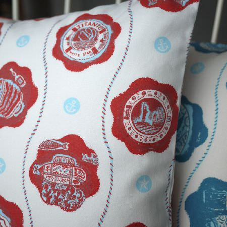 St Judes -  Jonny Hannah Fabric Collection - White cushions with red and blue rope stripes, blue dots with anchors/starfish, and blue/red patches, each with a different nautical image