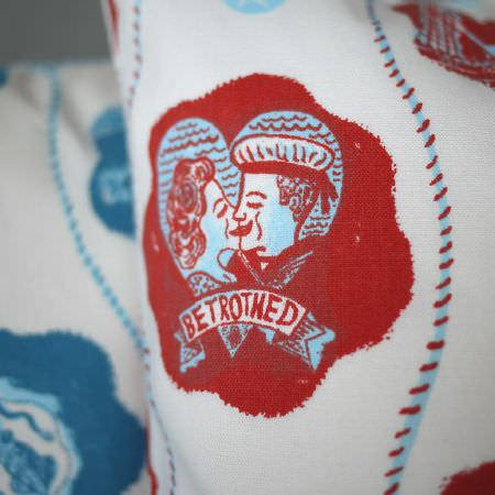 St Judes -  Jonny Hannah Fabric Collection - Close-up detail of a red, white and blue nautical cushion, featuring a scene of a
