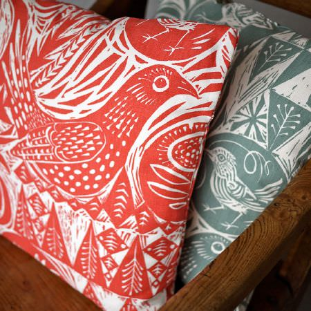 St Judes -  Mark Hearld Fabric Collection - Red and white cushion with a large bird design and smaller leaf designs, with the same print cushion in green and white, on a wooden chair