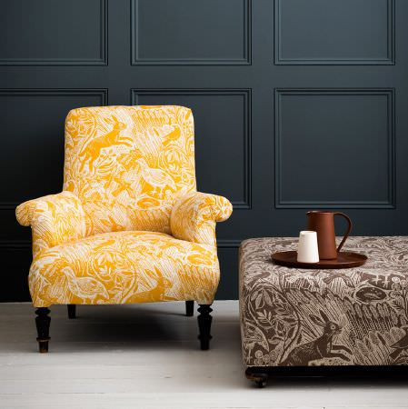 St Judes -  Mark Hearld Fabric Collection - Padded armchair covered in yellow and white hare and wild bird print fabric, with a brown and white matching footstool, brown tray and jugs