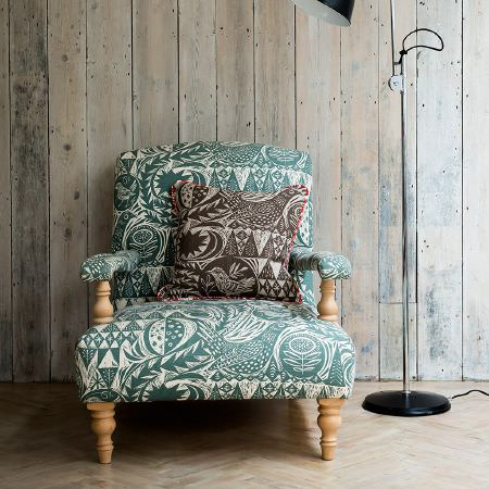 St Judes -  Mark Hearld Fabric Collection - Armchair with large green and white leaf and bird print, light wood legs and armrests, brown and cream leaf/bird print cushion, floor lamp