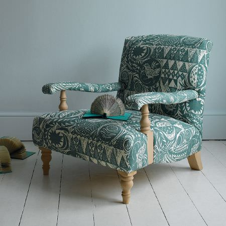 St Judes -  Mark Hearld Fabric Collection - Low armchair with large seat and carved light wood detail, padded with green and white bird and leaf print fabric