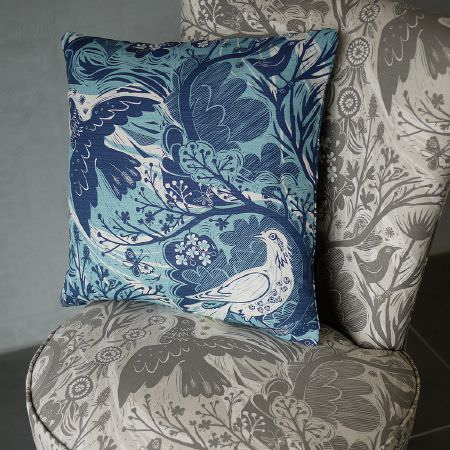 St Judes -  Mark Hearld Fabric Collection - Blue and white cushion with sweeping branches and birds, on a padded seat with the same patterned fabric but in grey and cream