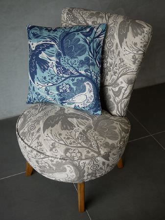 St Judes -  Mark Hearld Fabric Collection - Wooden-legged chair with round seat in grey and cream, with birds and branches, under a matching blue and white scatter cushion