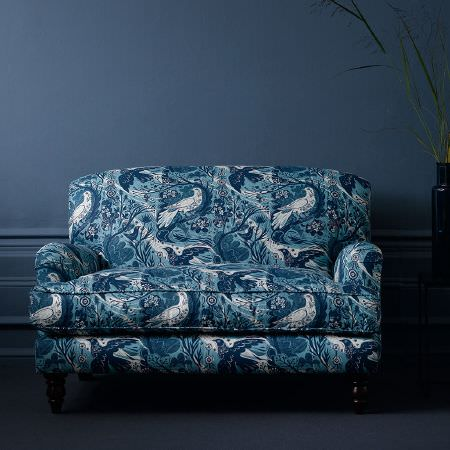 St Judes -  Mark Hearld Fabric Collection - Sofa with black carved legs, padded and covered with fabric featuring repeated blue and white pattern of birds, branches, flowers and leaves