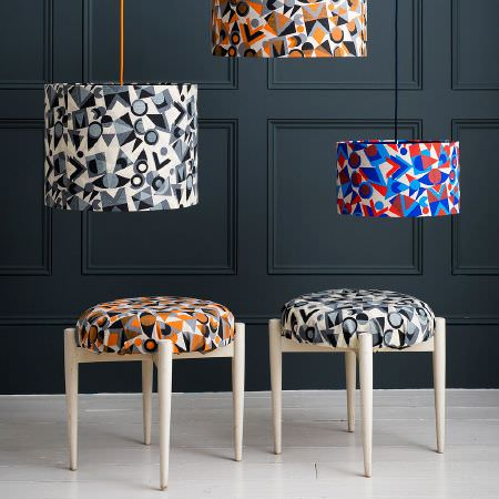 St Judes -  Peter And Linda Green Fabric Collection - Geometric print lampshades; one grey, black, white, with matching stool, one orange, black, grey, with matching stool, one red and blue