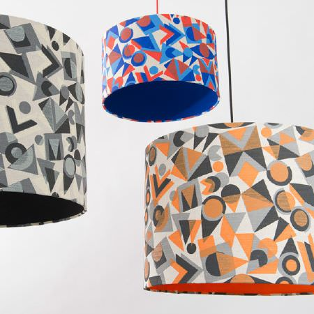 St Judes -  Peter And Linda Green Fabric Collection - Red, blue and cream geometric print lampshade, one orange, grey and cream geometric lampshade, one black, grey and white geometric lampshade