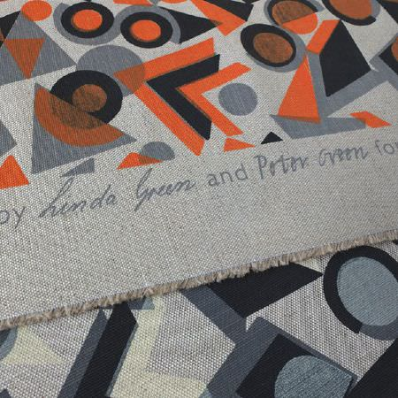 St Judes -  Peter And Linda Green Fabric Collection - Grey, black and orange geometric print fabrics, with a strip of grey fabric with text with people