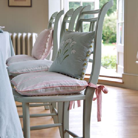 Susie Watson Designs -  Susie Watson Designs Fabric Collection - Kitchen chairs with pink striped cushions with edging and ties plus bobble-edged eau de nil cushion with flower.Pale blue tablecloth.