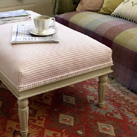 Susie Watson Designs -  Susie Watson Designs Fabric Collection - Footstool with candy-pink striped fabric, sofa with muted red and green squares  and a cream self-striped cream cushion with dotted edging.