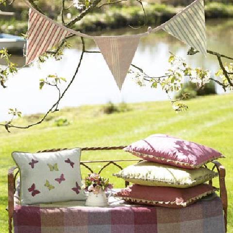 Susie Watson Designs -  Susie Watson Designs Fabric Collection - Bunting with pastel striped fabric. Garden bench with pink-square pattern throw and edged cushions in pink, yellow and a butterfly pattern.