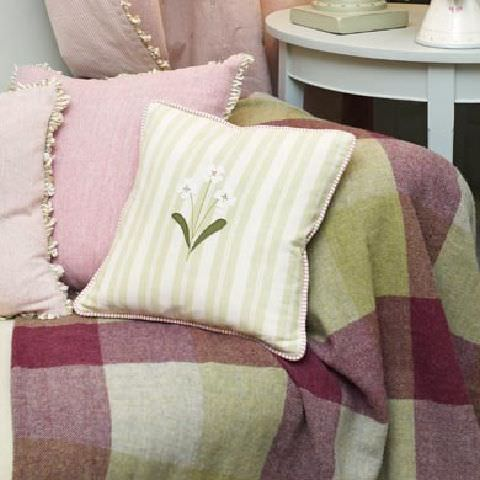 Susie Watson Designs -  Susie Watson Designs Fabric Collection - Throw with shades of red and green squares; two pastel pink cushions with fringes and a pale green and white striped cushion with daisy.