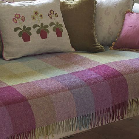 Susie Watson Designs -  Susie Watson Designs Fabric Collection - Throw with shades of red, blue and green squares with fringe. Neutral cushion with flowers in pots and one green and one shiny pink cushion.