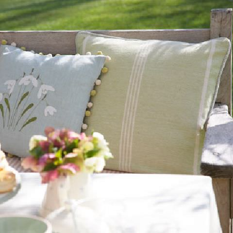 Susie Watson Designs -  Susie Watson Designs Fabric Collection - Garden seat with pale green cushion with white stripes and piped edging and a pale blue cushion with embroidered flowers and bobble fringe.