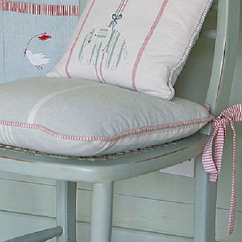 Susie Watson Designs -  Susie Watson Designs Fabric Collection - Kitchen chair with cushions in pastel shades of blue, cream and eau de nil with piped edging. One cushion with pink striped ties.