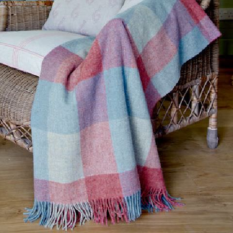 Susie Watson Designs -  Susie Watson Designs Fabric Collection - Wicker chair with neutral seat cushions with pastel pink pattern. Fringed throw with squares in shades of pink and blue.