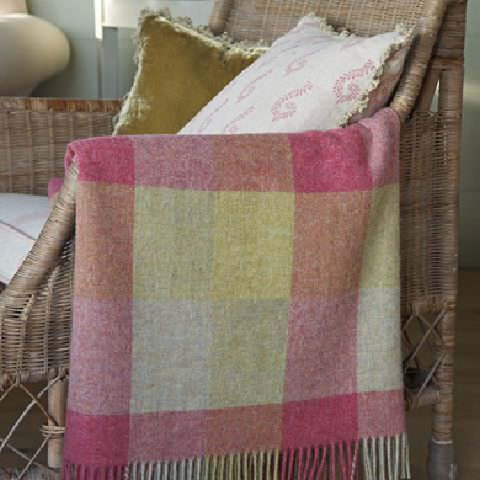 Susie Watson Designs -  Susie Watson Designs Fabric Collection - Garden chair with fringed throw with pink, yellow and beige squares, a sage green cushion with fringe and pink patterned cushion.