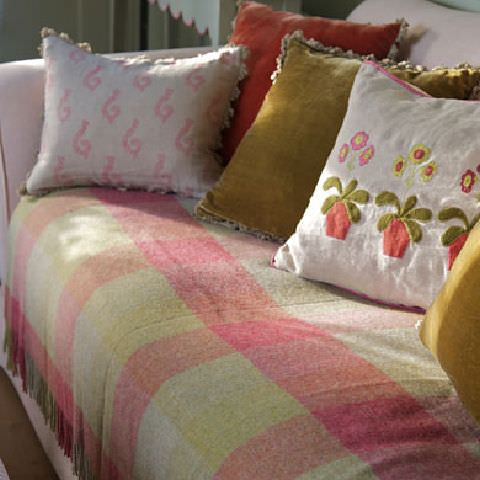 Susie Watson Designs -  Susie Watson Designs Fabric Collection - Sofa with fringed throw with red, green and beige squares. Fringed cushions in plain green, pink and floral.