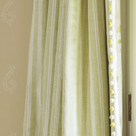 Susie Watson Designs -  Susie Watson Designs Fabric Collection - Vertically striped light green and white curtains with green and white pompom edging, in front of a white and cream backdrop