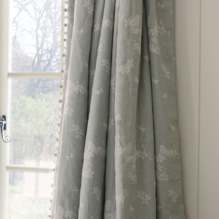 Susie Watson Designs -  Susie Watson Designs Fabric Collection - Light grey curtains made with a small pale grey floral design and an edging of small white and grey pompoms