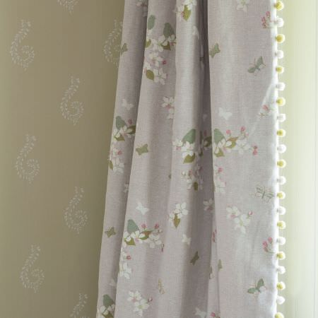 Susie Watson Designs -  Susie Watson Designs Fabric Collection - A white and beige patterned surface behind white, green, pink and grey floral and butterfly print curtains with pompom edging