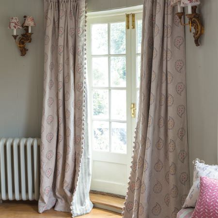 Susie Watson Designs -  Susie Watson Designs Fabric Collection - White floor-length curtains with fringed edges and a simple floral paisley print, with patterned cushions and wall sconces