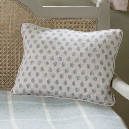 Susie Watson Designs -  Susie Watson Designs Fabric Collection - A pale blue and white dotted scatter cushion on a white wood chair with a wicker back and a pale blue and white checked seat