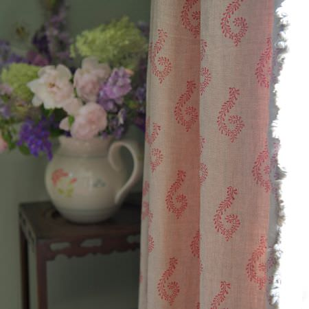 Susie Watson Designs -  Susie Watson Designs Fabric Collection - A white jug used as a vase on a square occasional table, behind cream fringed curtains with a repeated pink pattern