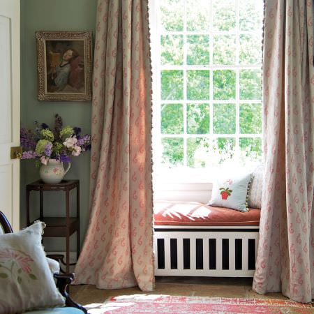 Susie Watson Designs -  Susie Watson Designs Fabric Collection - Long pink and white patterned curtains with fringed edges, a red window seat, floral cushions, a small table and a jug vase
